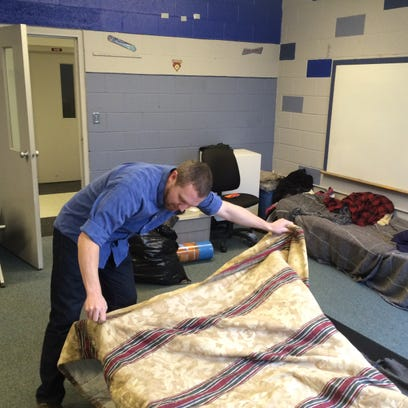 The Rev. Chad Gibbsons makes a bed in the Centerpointe