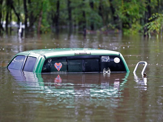A vehicle is flooded following heavy rains and flash flooding along Black Creek in Florence, S.C., Monday.