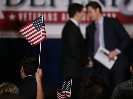 A woman waves an american flag as presidential hopeful Marco Rubio is introduced at the Defend and Reform town hall series on Thursday, Dec. 10, 2015, in West Des Moines.