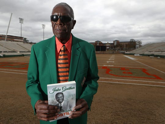 Roosevelt Wilson holds a copy of his book, a biography on legendary FAMU coach Jake Gaither, at Bragg Memorial Stadium on the university's campus Wednesday, Jan. 10, 2018.