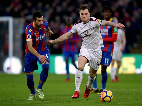 Crystal Palace's Luka Milivojevic, left, and Burnley's Ashley Barnes battle for the ball during the English Premier League soccer match at Selhurst Park, London, Saturday Jan. 13, 2018. (Daniel Hambury/PA via AP)