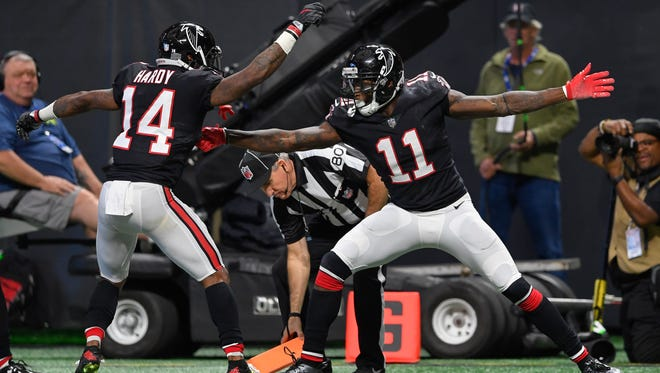 Atlanta Falcons wide receiver Julio Jones reacts with wide receiver Justin Hardy after catching a touchdown pass against the Tampa Bay Buccaneers during the first half at Mercedes-Benz Stadium.