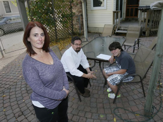 Eliza Marroni, 41, left, said she quit her nursing job at the Michigan Department of Health & Human Services' Hawthorn Center psychiatric hospital because of the stress caused mandatory overtime. She's seen in this Oct. 1 photo with her husband, Christopher Marroni, 41, and their son, Vincent Marroni, 13, in the backyard of their Plymouth home. Marroni said she missed Vincent's hockey tournaments because of overtime.