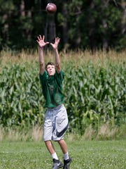 A Colby football player catches a pass during practice,