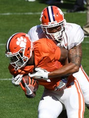 Clemson safety Isaiah Simmons (11) wraps up running back Travis Etienne (9) during the team's practice on Wednesday, April 4, 2018 at Clemson's Memorial Stadium.