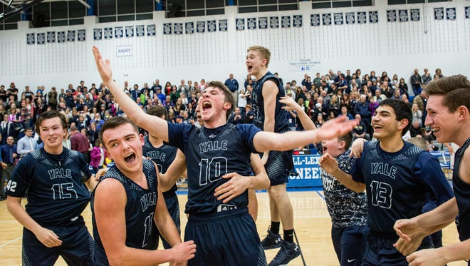 Yale senior Cody Kegley, center, screams and is surrounded by teammates after he scored the winning shot, beating Cros-Lex in a district final basketball game Friday, March 11, 2016 at Cros-Lex High School.