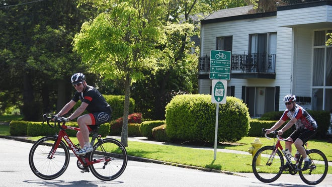 Cyclists ride past a Scenic Bikeway sign along Winter Street NE in Salem. City planners are considering creating bicycle-first roadways in low-traffic neighborhoods throughout town.