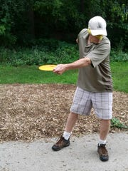 St. Cloud disc golfer Tim Mackey throws a tee shot blindfolded during a round of disc golf at Calvary Hill Park.