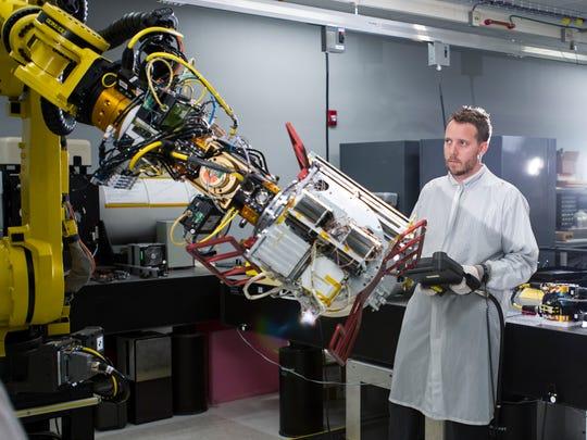 Raytheon employee Tony Vulcano uses a robot to carry