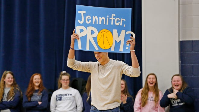 Harrison High School senior Dre Boyles surprises everyone as he walks onto the floor of McHale Gymnasium to ask Jenni Harkcom, a senior member of the Central Catholic girls basektball team, to the prom during a pep rally for the team Friday, February 26, 2016, at Central Catholic High School. CC will face Covenant Christian in the Class 2A State Championship Saturday at Bankers Life Fieldhouse in Indianapolis. Harkcom said yes to Boyles' request.