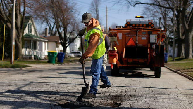 Ray Magley, with the Green Bay Department of Public Works, patches potholes in Green Bay.