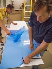 Matthew Smith and John Freek remove protective coating