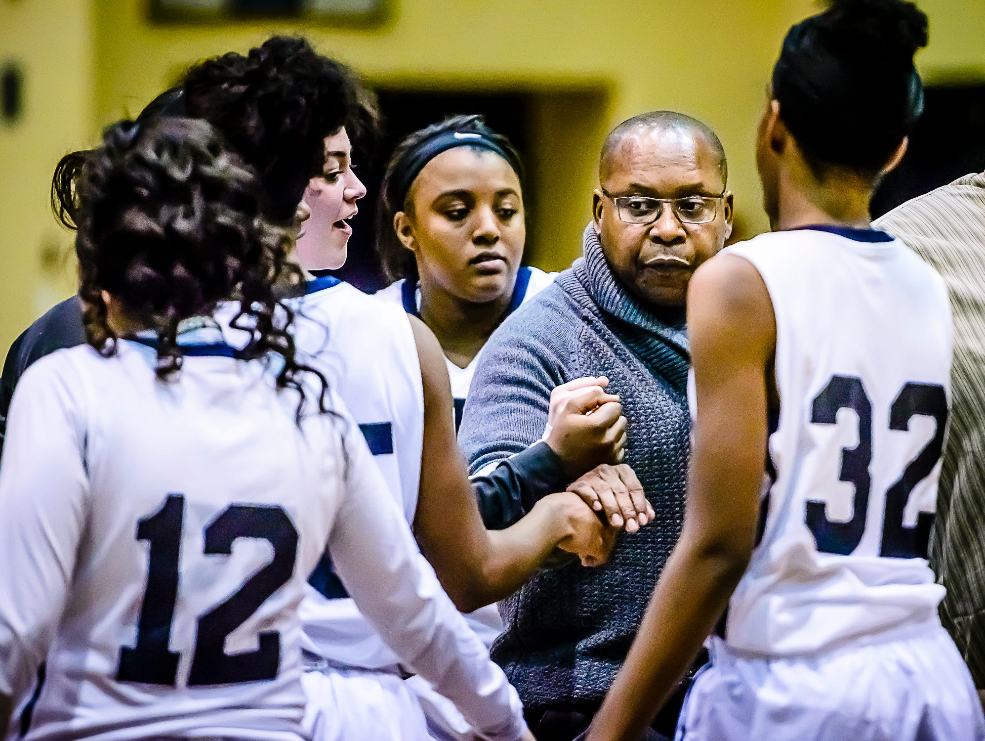 Eastern Girl's Basketball Head Coach Curtiss Wright huddles with his team in a timeout during their game with Jackson Tuesday January 10, 2017 in Lansing. KEVIN W. FOWLER PHOTO