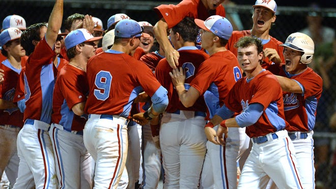 J.L. Mann's Joe Satterfield (2) is met at home plate by his teammates after hitting a home run against T.L. Hanna in the seventh inning of the visiting Patriots' 7-3 win in the Class AAAA Upper State tournament Monday night.