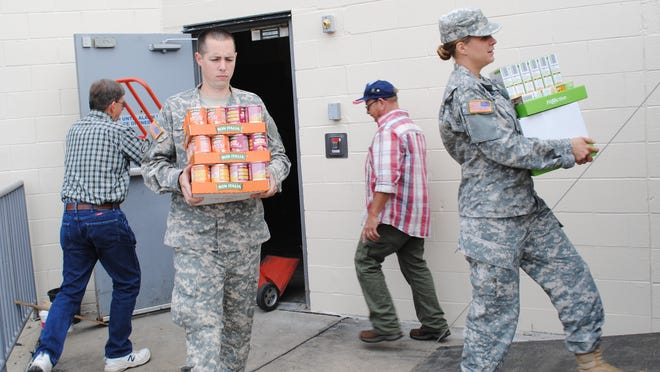 "Volunteers from the National Guard and the Grand Ledge Lions Club load cases of food into a truck for delivery to Sawdon School in Grand Ledge to be used by the ""Blessings in a Backpack"" program."