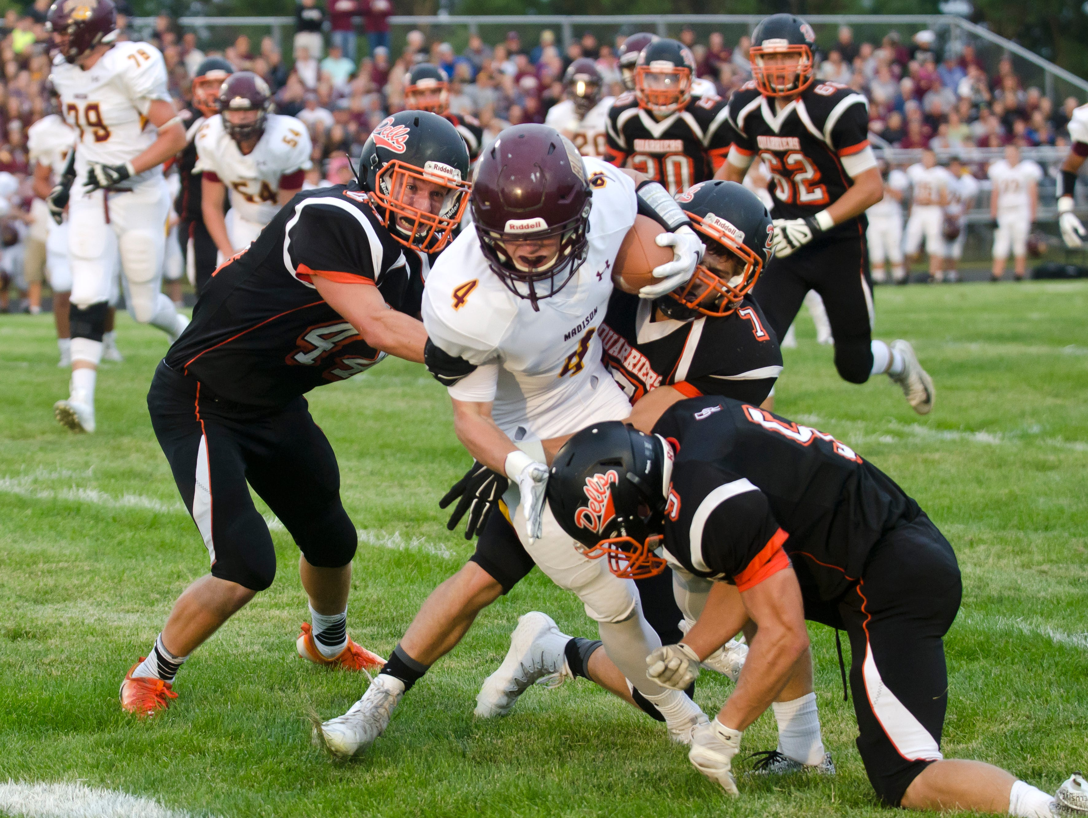 Madison's Mason Leighton is gang-tackled by Dell Rapids' Tanner Heim (44), Ross Wiebenga (7) and Anthony Miller (5) Friday, Aug. 26, at Dell Rapids.