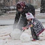 Brandon Bruscato and his daughter Elizabeth make a snowman in the front yard along Spencer Avenue. Monroe is covered in a blanket of white on Wednesday as snow falls across northeastern Louisiana.