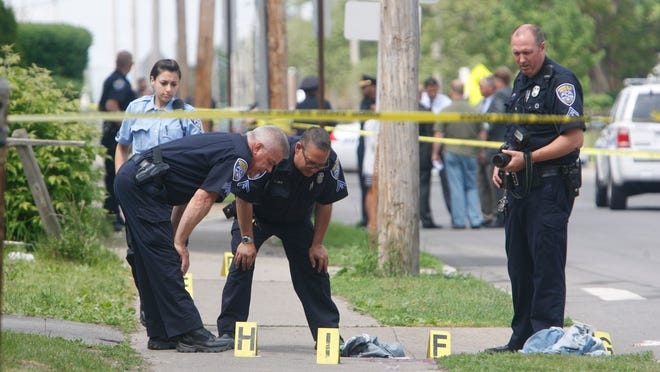 Rochester police look over the area where a 29-year-old man fell on Bay Street after running around the corner from Sixth Street after being shot several times on May 26.