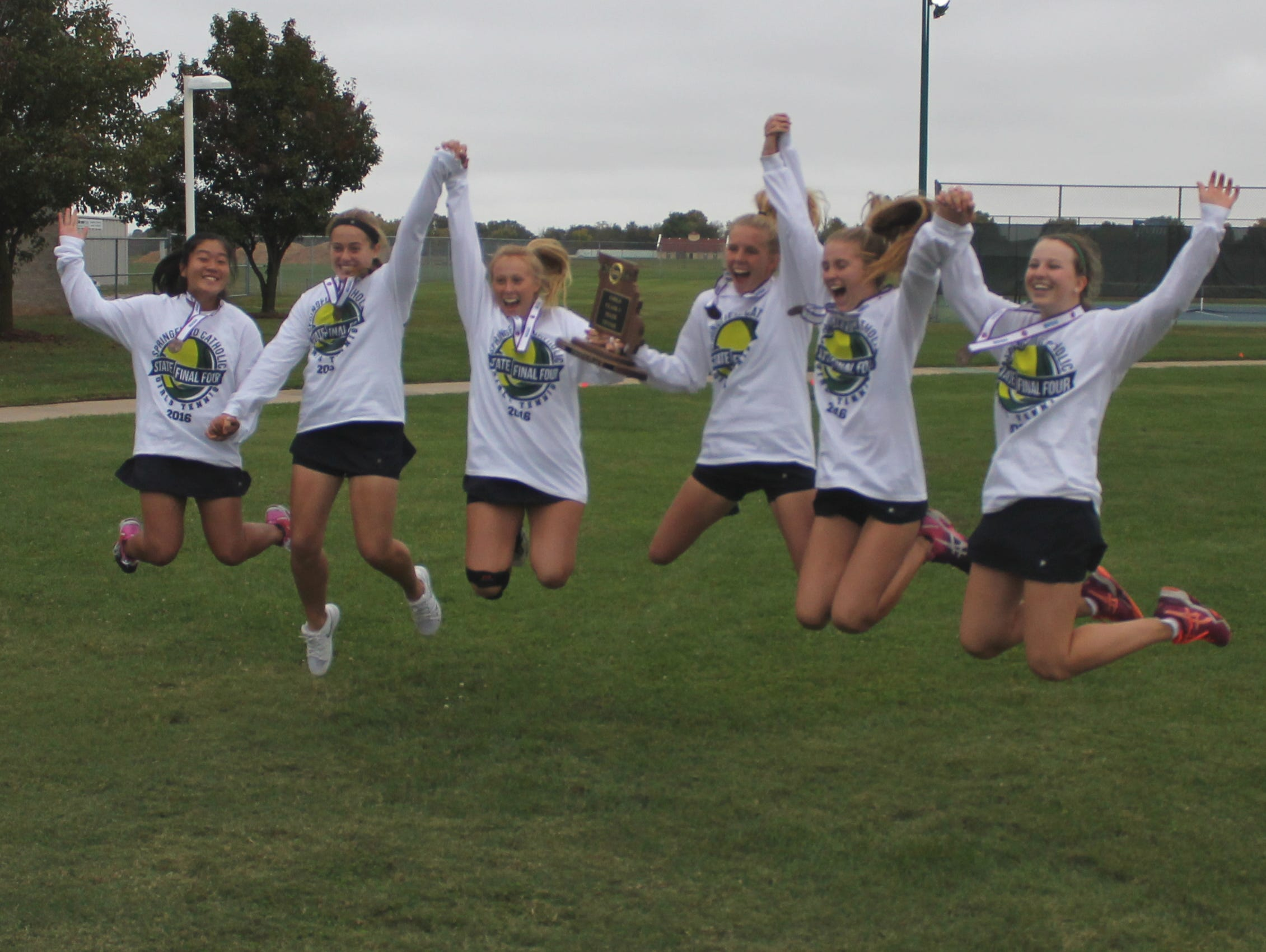 Springfield Catholic's top six tennis players jump in the air to pose for a celebratory photograph after winning fourth place in the 2016 state team tennis tournament at Cooper Tennis Complex.