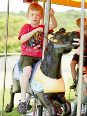 Six-year-old William Boodley-Buchanan, of Groton rides the Stewart Park Carousel the July 3 in Stewart Park. Boodley's mother, Ithaca native Jeanne, has memories of riding the carousel when she was a child.