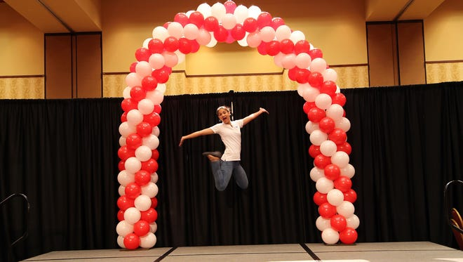 Crystal Routon jumps for joy under an arch of balloons from Creativity in Balloons and Events, a small business that she and her father, John Iden, run in Murfreesboro.