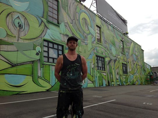 Artist Ian Ross posing in front of his new mural in