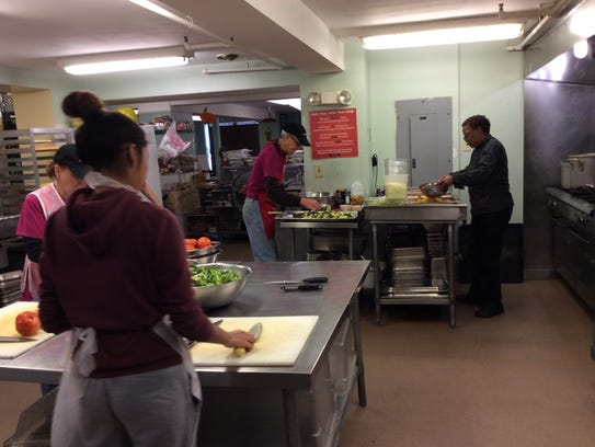 Chef Pam Johnson, right, and volunteers, prepare a