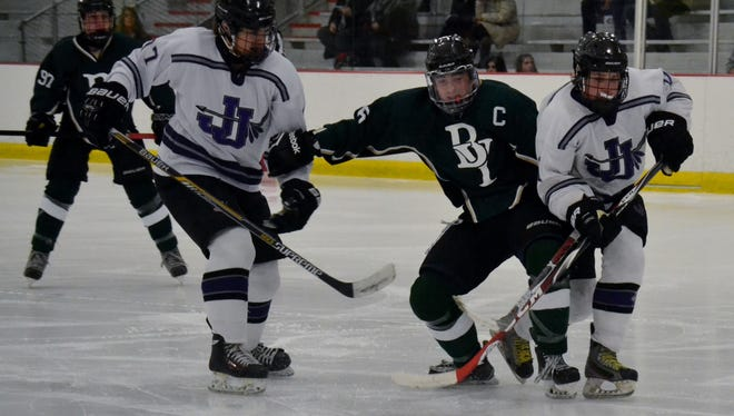 Brewster/Yorktown defenseman Connor Henderson (center) fights for a loose puck Sunday during a 7-4 loss to John Jay at Brewster Ice Arena.
