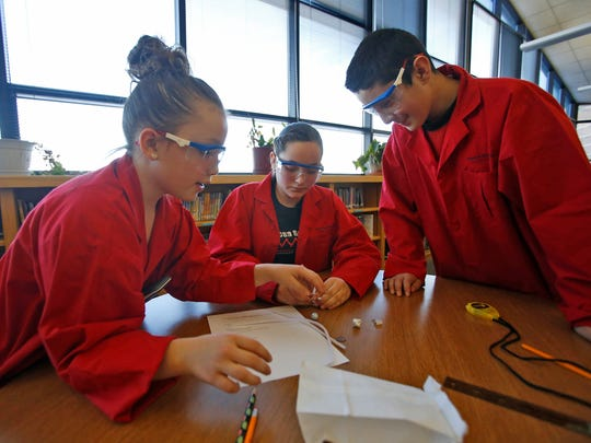 Hermosa Middle School students Isabella Chavez, left, Ana Munez and Ezequiel Borunda take part in the experimental design competition Saturday during the 2016 Northwest Regional Science Olympiad at Mesa View Middle School in Farmington.