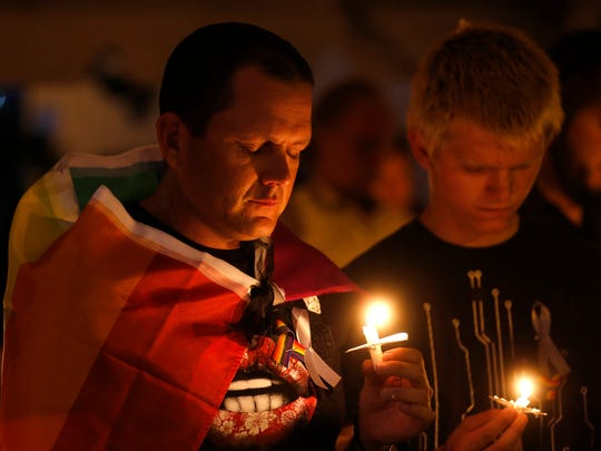 Allen Hicks, left, and Lance Kesterson close their eyes on Monday at Orchard Park in Farmington during a candlelight vigil to remember the victims of a mass shooting at a nightclub in Orlando, Fla.