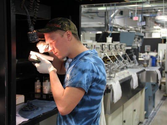 Optician Jesse Mottler inspects a high precision optical