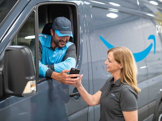 An Amazon delivery driver conversing with a fellow employee.