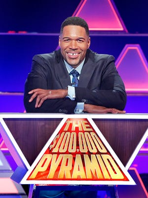 """Michael Strahan hosts the second season of ABC's """"The $100,000 Pyramid,"""" which premieres June 11. Packers quarterback Aaron Rodgers is among the celebrity players."""