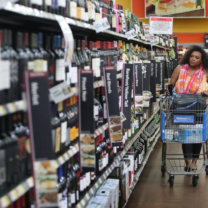 July 1, 2016 - Quinn Gee makes her way down Walmart's newly opened wine aisle at the Whitehaven location. On Friday morning grocery stores across Tennessee could begin selling wine.  (Stan Carroll/The Commercial Appeal)