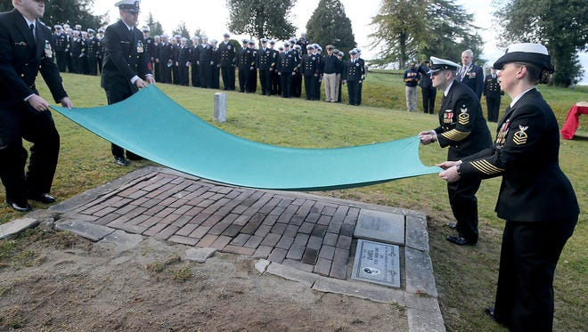 "A cover is lifted to unveil the new marker for Chief Gunner's Mate John "" Dick"" Turpin at Ivy Green Cemetery in Bremerton on Friday. He was stationed on the USS Maine when it exploded in Havana, Cuba, in 1898 .The Bremerton native had a Navy burial at sea."