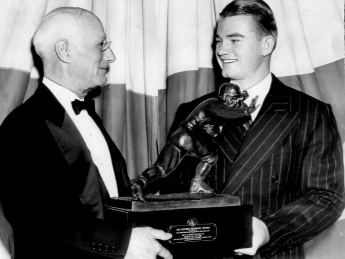 Nile Kinnick, right, holds the Heisman Trophy in 1939.