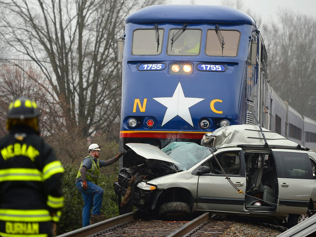 Officials investigate an accident between the 1755 Amtrak passenger train and a Dodge Caravan where the female driver of the van was killed in Mebane, N.C.  The collision occurred at the Fourth Street crossing in downtown Mebane but the van was ultim