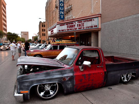 A lowered 1987 Chevy Silverado C-10 is parked next to the Paramount Theatre during Thursday's CarWalk. The monthly ArtWalk event featured automobiles along Cypress Street.
