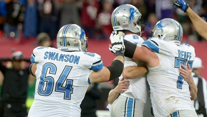 Detroit Lions offensive linemen Travis Swanson, left, and Riley Reiff, right, celebrate a win Oct. 26, 2014.