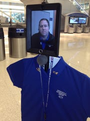 The face and voice of guest services director Brian Eckstein cruises through the Indianapolis International Airport on Thursday, Oct. 9, 2014, the first day of the customer-service robot's official rollout.