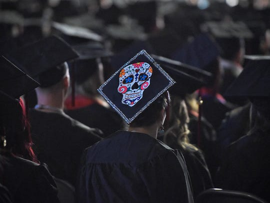 A graduate's mortar board is decorated in bright colors during Friday's fall semester commencement ceremony at St. Cloud State University's Halenbeck Hall.