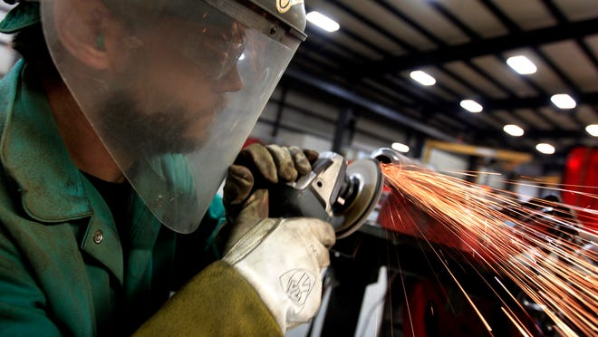 Travis Janssen grinds the end of a pipe smooth while working at Piping Systems Inc. on October 13 in Hortonville.