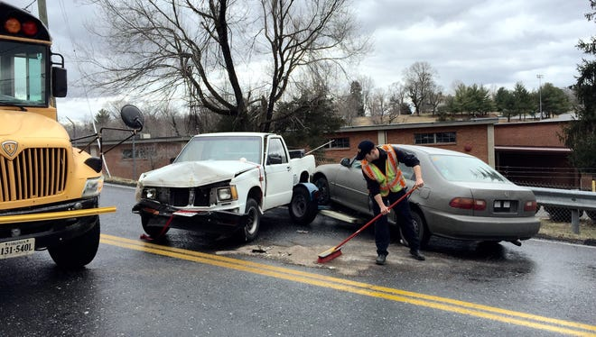 A Staunton fire and rescue officer cleans up at a Staunton school bus accident at Chrysler Street near Hayes Avenue on March 11, 2015.
