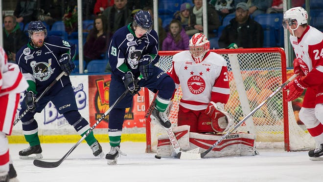 Plymouth Whalers center Cullen Mercer (No. 19) gets out of the way of a shot Saturday night, but Sault Ste. Marie goalie Brandon Halverson is there to stop it. At left for Plymouth is Victor Crus Rydberg (No. 16).