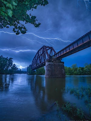 Lighting crashes across the sky Sunday morning over the Arkansas River and the train bridge between Van Buren and Fort Smith. Winslow-based photographer Joel Ledbetter captured the image from the north side of the river Sunday. Today's forecast calls for partly cloudy skies with a high of 99 degrees and a low of 75.