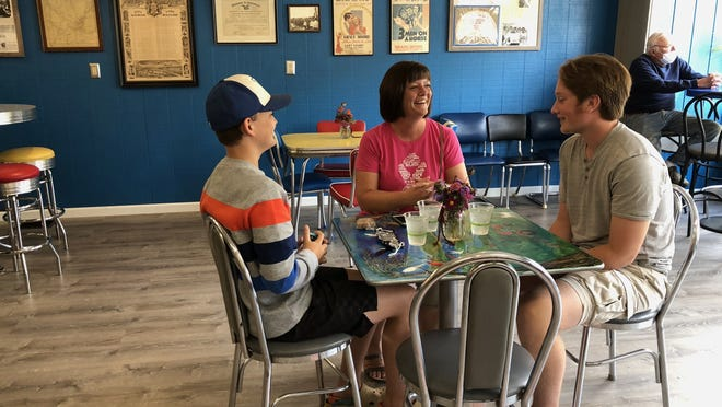 Carrie Grove is flanked by sons Grady and Charlie at the newly opened Caruso's Cafe on Main Street, Naples.