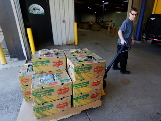 Sheboygan County Foodbank volunteer Brandon Roethel pulls a skid of produce delivered by the St. Luke Methodist Food Pantry to the the county bank in November.
