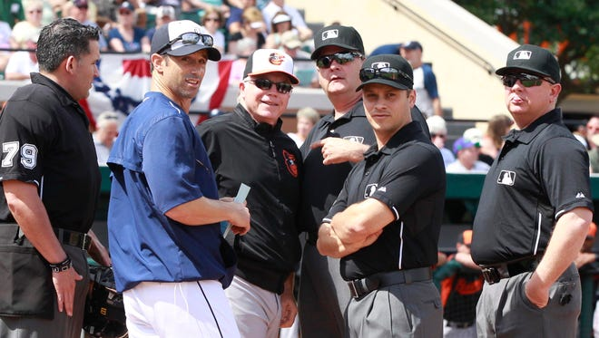 Detroit Tigers manager Brad Ausmus and manager Buck Showalter go over the rules with the umpires before their baseball game.