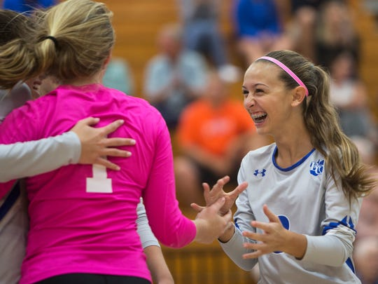 Olivia D'Agostino, #3, right, smiles with excitement as she goes to hug her teammates after scoring a point in a Class 7A regional quarterfinal volleyball game against Estero at Barron Collier High School on Tuesday, Oct. 25, 2016 in Naples, Florida. Barron Collier would go on to win 3-0, advancing to the regional semifinal game.