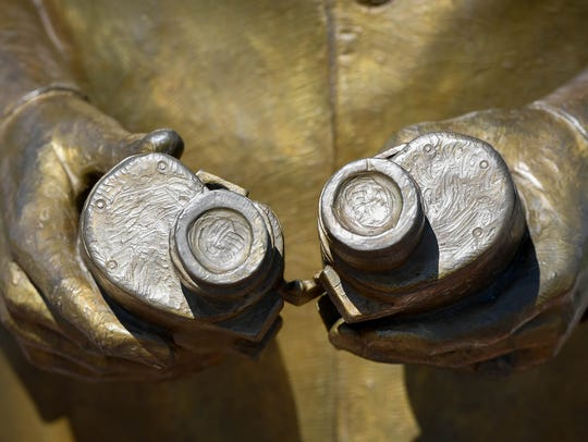 The binoculars on Admiral Husband E. Kimmel's riverfront statue show the missing hinge and the misalignment Wednesday.